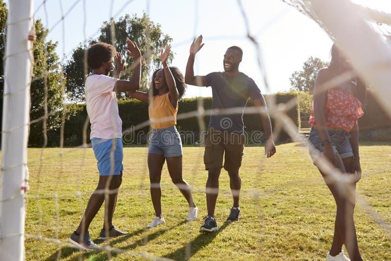 Haute adulte noire cinq d'amis pendant un jeu fun du football image stock