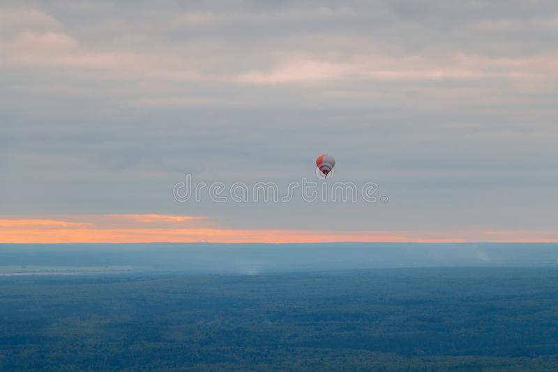 Haute colorée de ballon au-dessus de la terre dans le ciel au coucher du soleil en brouillard image libre de droits