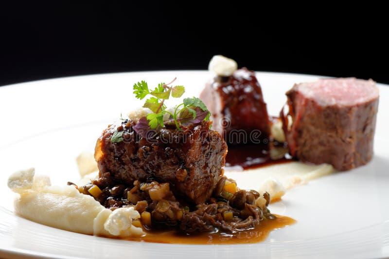 Haute cuisine, filet grillé de veau, queue de veau avec de la sauce du port, morelles, lentilles images stock