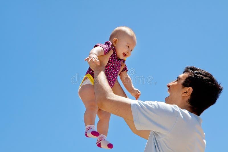 Haute de levage de bébé de papa dans le ciel photo stock