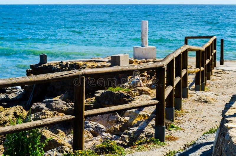 Haute falaise au-dessus de la mer avec la barrière en bois, backgro de mer d'été photos stock