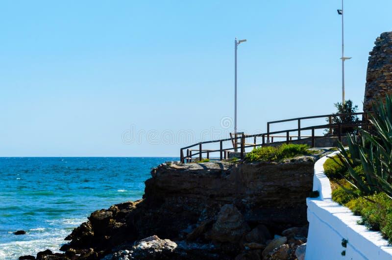 Haute falaise au-dessus de la mer avec la barrière en bois, backgro de mer d'été photographie stock