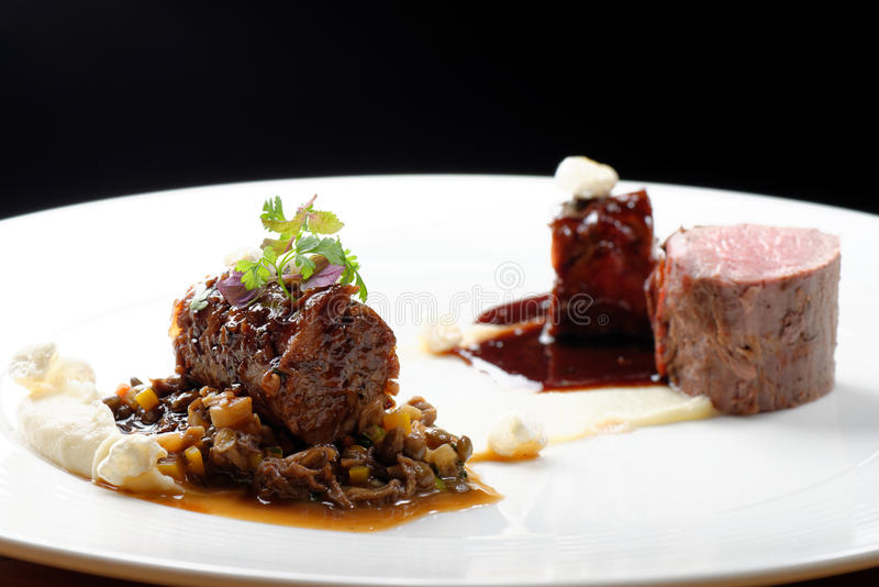 Haute kokkonst, grillad kalvköttfilébiff, kalvköttsvans med en sås av port, morels, linser royaltyfri fotografi