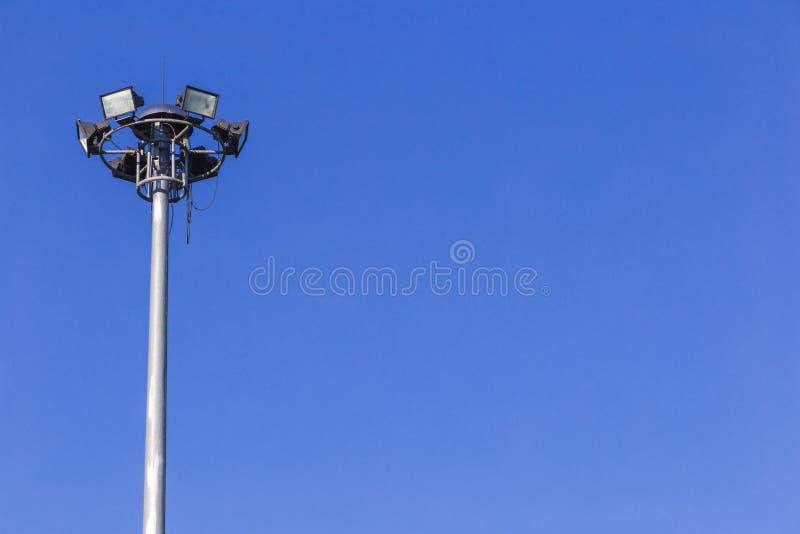 Haute tension de tour de projecteurs dans le stade de sport sur le fond de ciel bleu photo libre de droits
