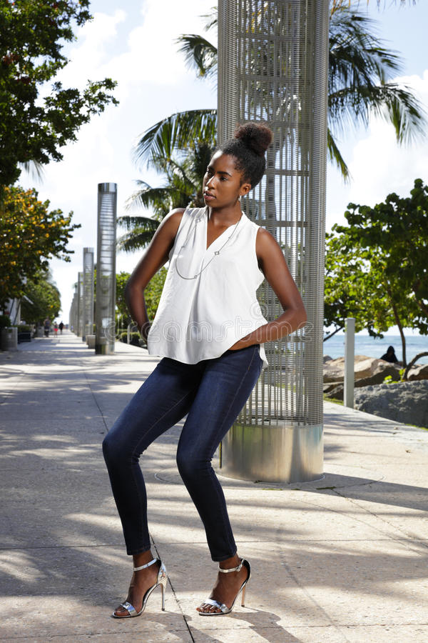 Hautecouture-Modell, das in den dünnen Jeans in der Parkafroamerikanerschönheit aufwirft stockfoto