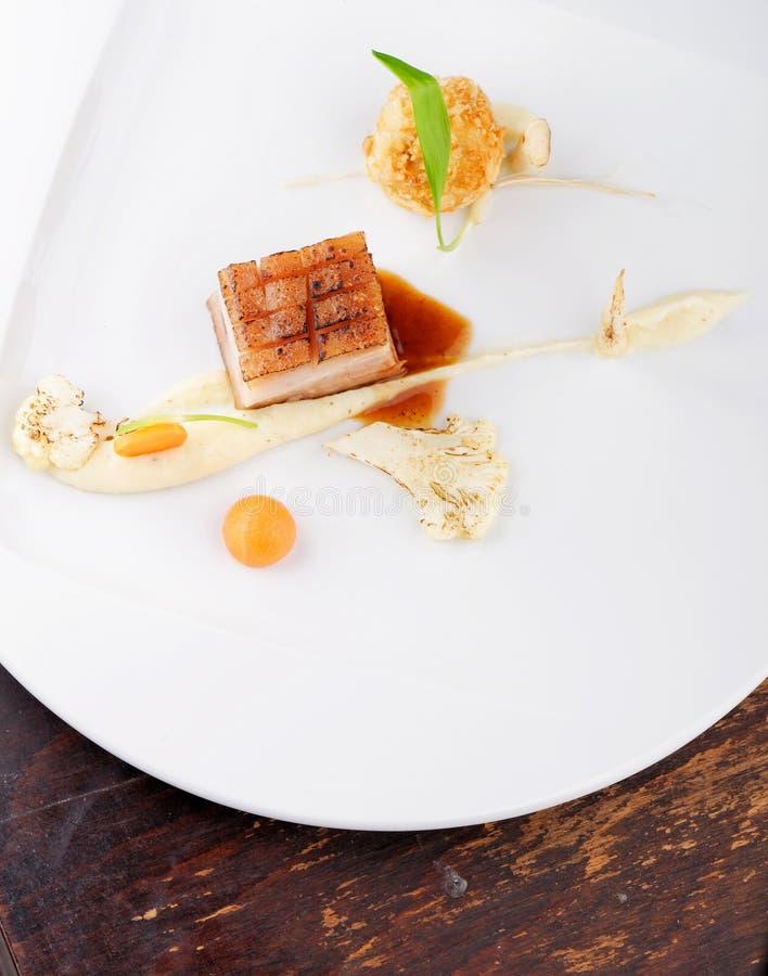 Hautekeuken, het lapje vlees van Varkensvleesconfit met een aardappel stock foto