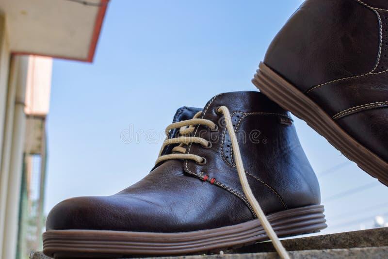 Hautes chaussures brunes foncées de cheville pour les hommes et prêt à porter images stock