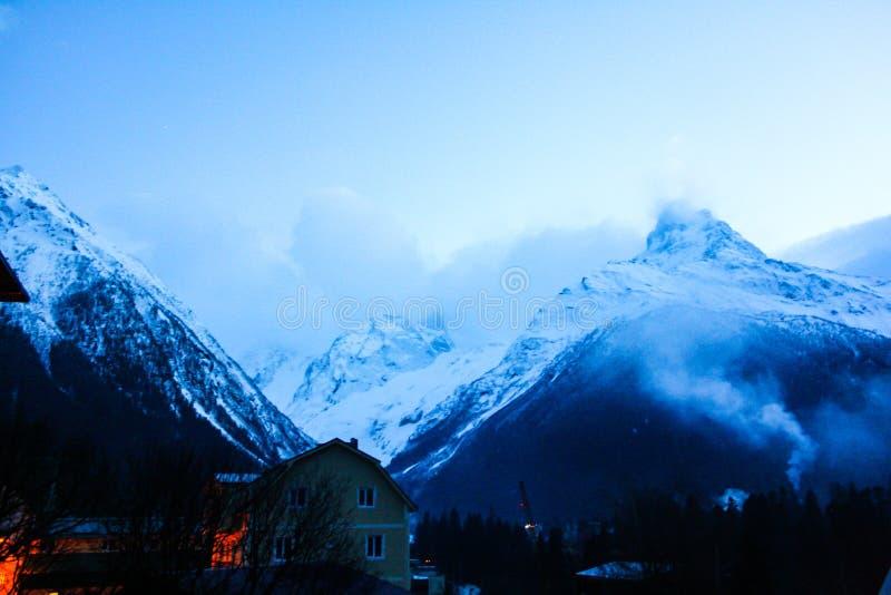 Hautes montagnes couronnées de neige en brouillard images libres de droits