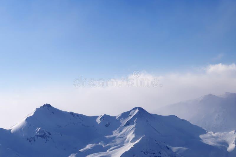 Hautes montagnes neigeuses en brume et ciel nuageux ensoleillé à la soirée d'hiver photos stock