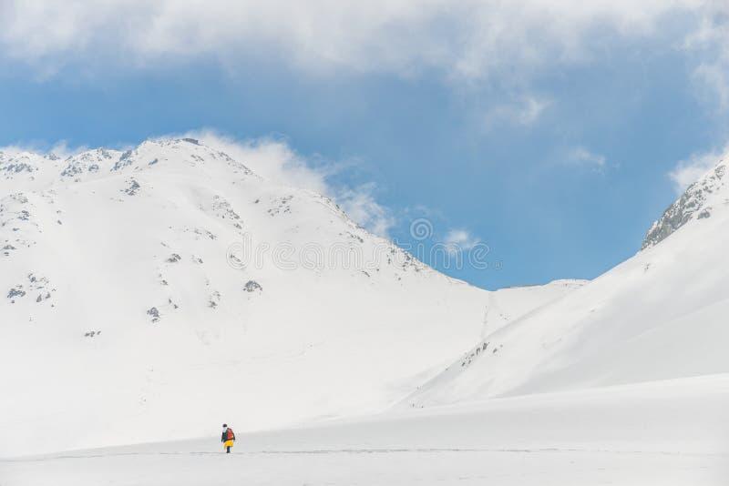 Hautes montagnes sous la neige avec le ciel bleu et la hutte clairs image stock
