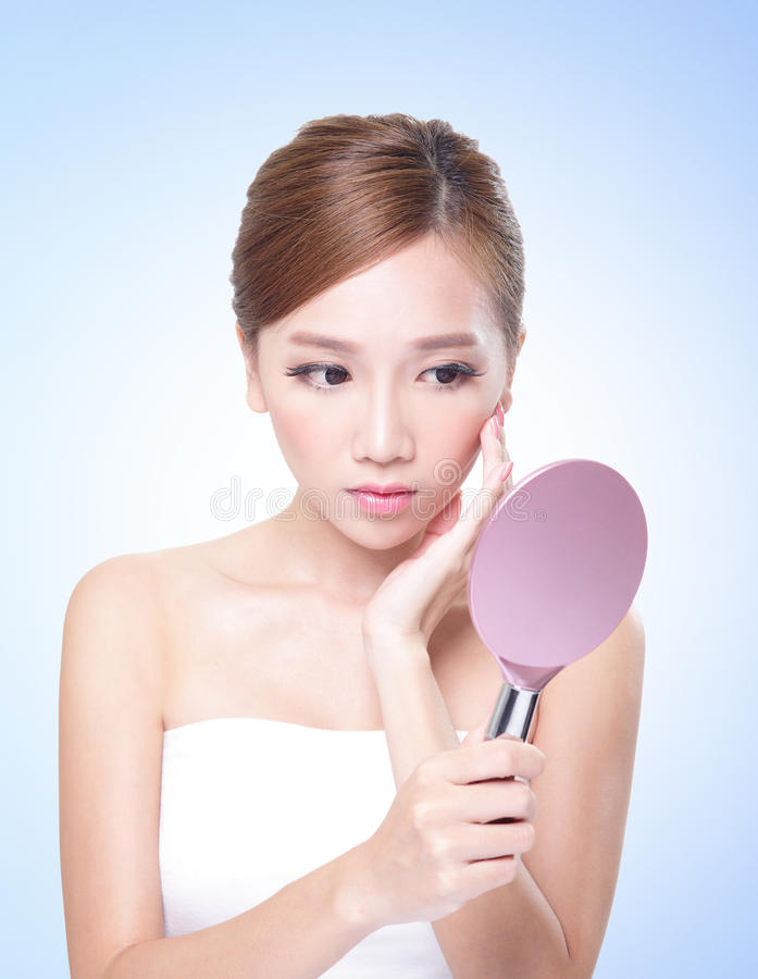 Hautpflege-Frau, die mit Spiegel betrachtet lizenzfreie stockfotos