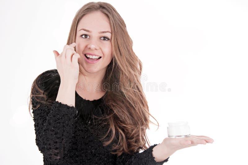 Hautpflegefrau, die Gesichtssahne setzt stockfotografie