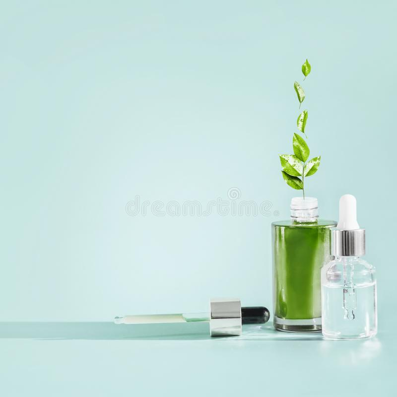 Hautpflegekosmetikflasche mit Tropfenzähler und Pipette am blauen Hintergrund Natürliche Serum- oder Erdölerzeugnisse mit grünem  lizenzfreie stockfotos