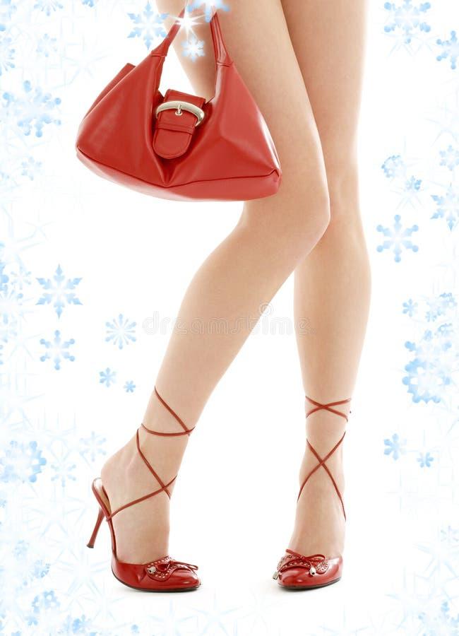 Hauts talons et bourse rouge avec des flocons de neige image libre de droits