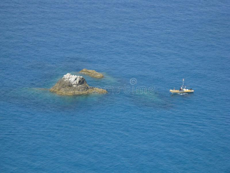 Hav med den steniga ön och fartyget arkivbild