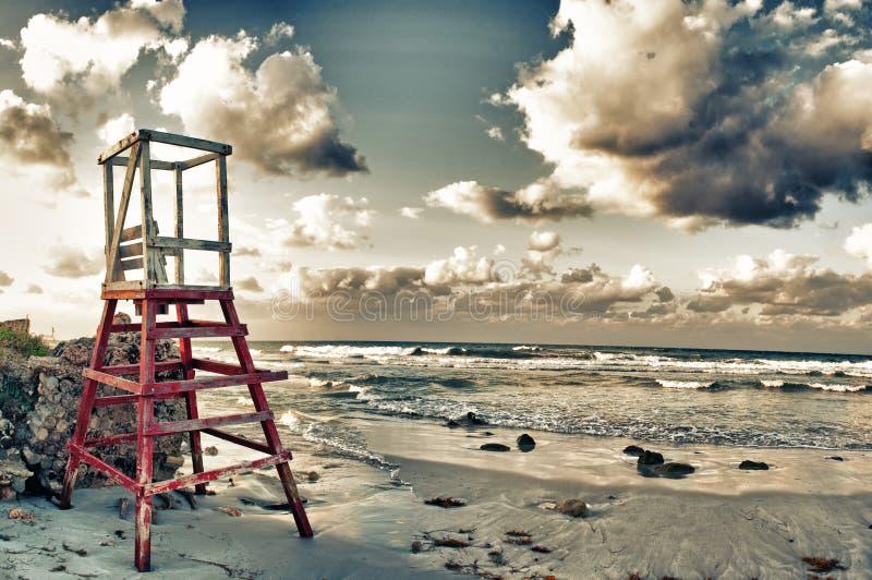 Hav på solnedgången med den övergav stolpen för livvakt i den Guanabo stranden, arkivfoto