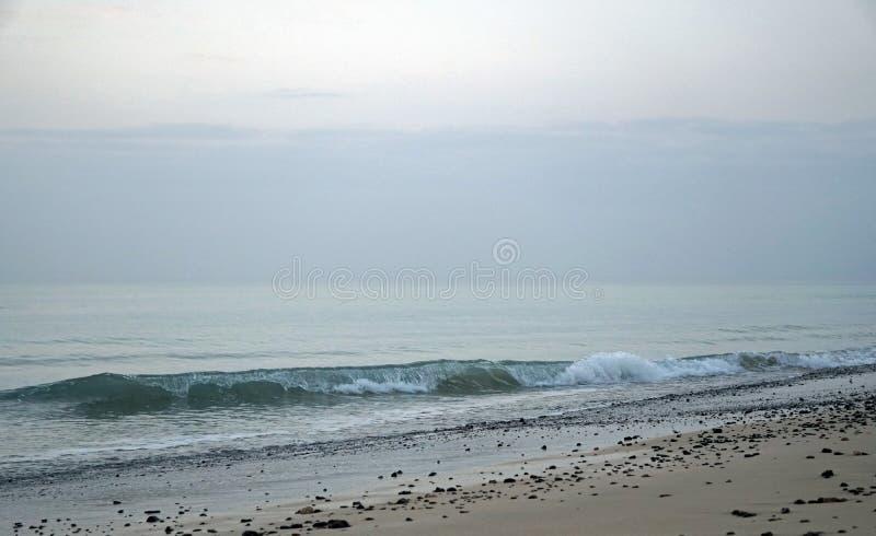 hav Rinnande bränning vinkar på stranden Tidigt på morgonen några minuter för soluppgång royaltyfri bild