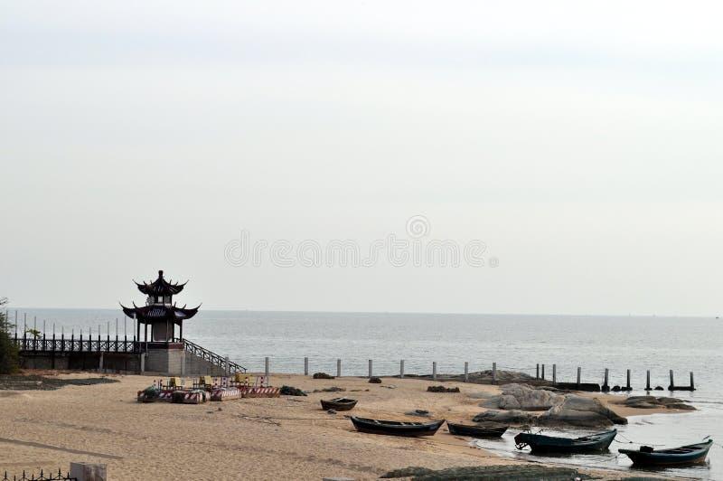 Hav, strand och forntida paviljonger arkivbilder