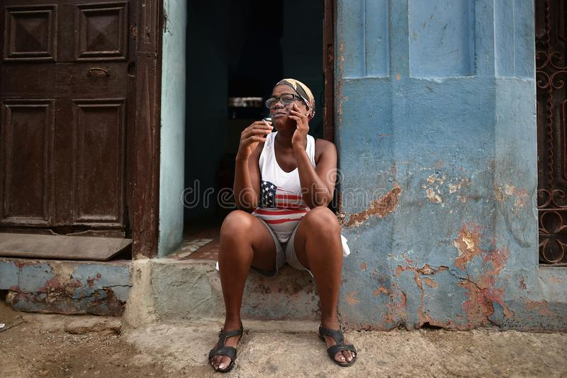 Havana, Cuba, August 14th, 2018: Woman sitting down and smoking on the streets of Havana. In Cuba stock photo