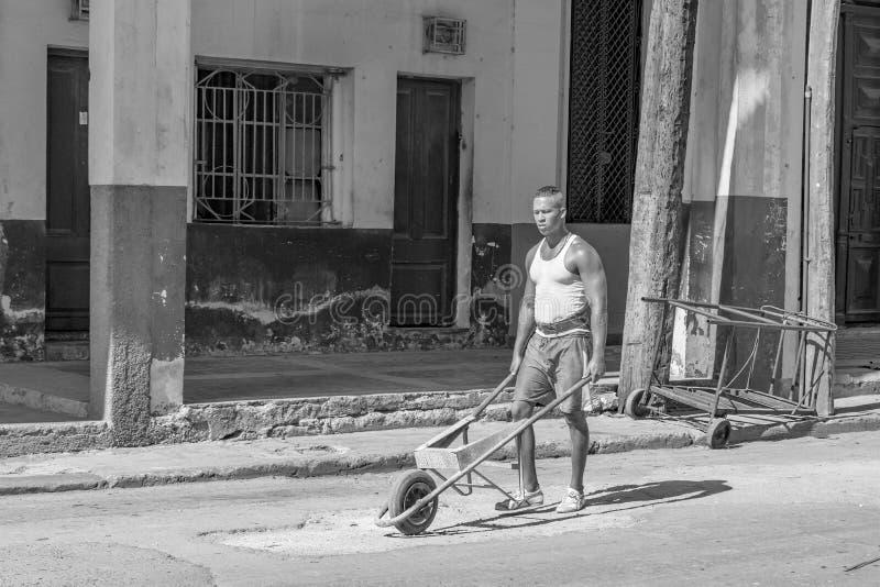 HAVANA, CUBA 29 de outubro - o homem rola o carrinho de mão de roda antiquado para o trabalho da construção nas ruas de Havana, o fotografia de stock