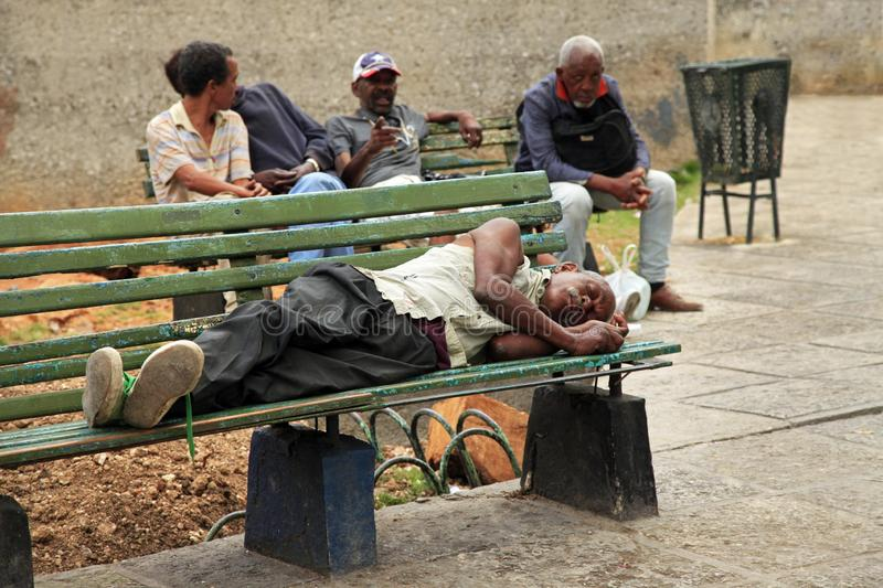 Homeless man lying on a bench in old Havana, Cuba royalty free stock images