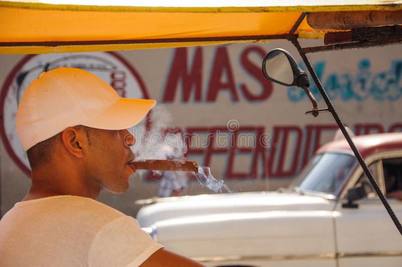 Havana, CUBA - JANUARY 20, 2013: Unknown young male taxi driver. Smoke cigar, in background old classic American car drive on street of Havana,CUBA on front of stock photo