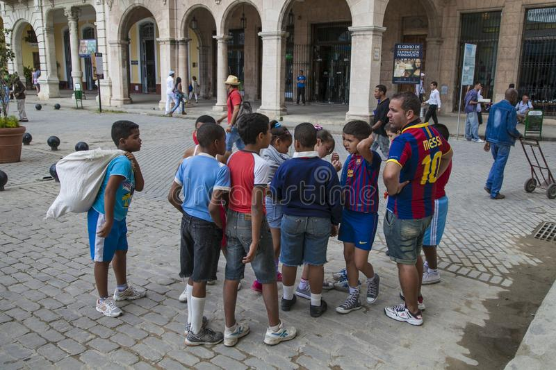 Havana, Cuba - 24 January 2013: A view of the streets of the city with cuban people. Many children are flocking to their educator royalty free stock photo