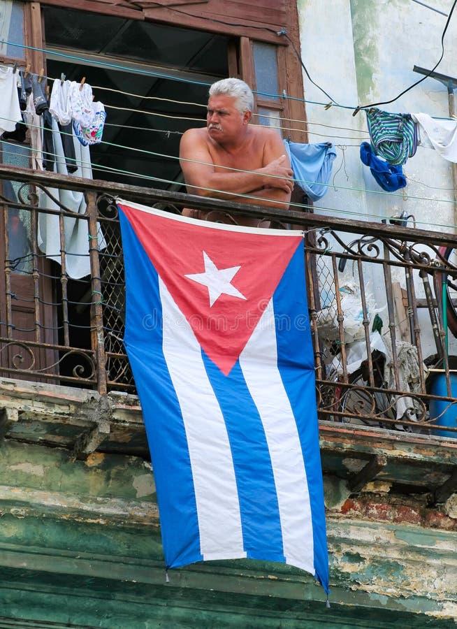 HAVANA,CUBA-JULY 26,2006: Man standing on the balcony with the Cuban flag royalty free stock photos