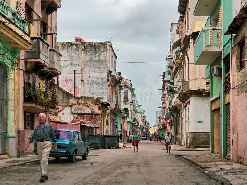 Wide shot of people walking in a narrow road near colorful old and new buildings in Havana, Cuba stock photography