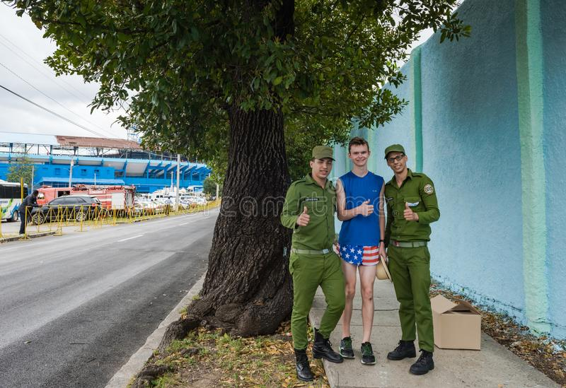 Cuban American Relationship. Havana, Cuba / March 22, 2016: American tourist, dressed in patriotic shorts, gives a thumbs up with two Cuban soldiers dressed in royalty free stock image