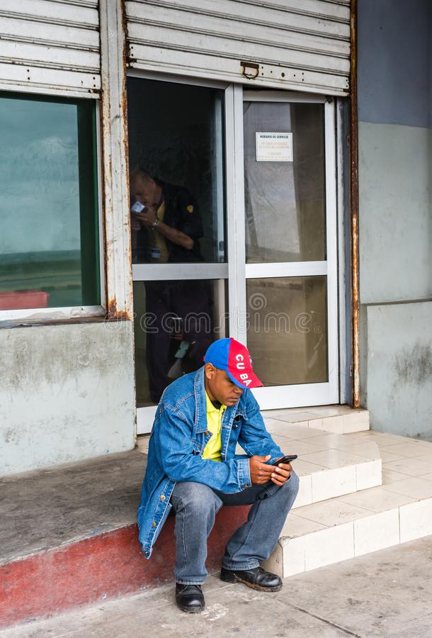 Cuban Man Using Smartphone. Havana, Cuba / March 21, 2016: Despite Cubas limited wifi connectivity, a man - wearing a Cuba baseball hat - sits on a doorstep stock photography