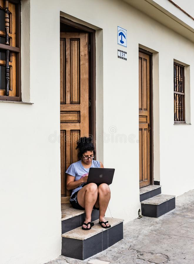 Woman Working on Cuban Doorstep. Havana, Cuba / March 21, 2016: Although Cuba has limited wifi connectivity, a woman works on a laptop at a hostel doorstep stock photo