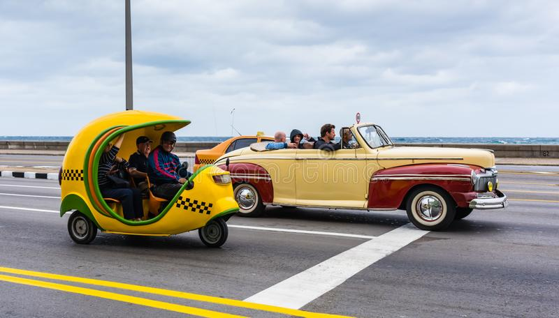 Three Cuban Taxis on the Malecon. Havana, Cuba / March 21, 2016: Three taxis on the Malecon highway in Havana, one is a vintage convertible and another is a mini stock images