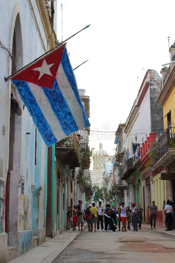 Havana, Cuba - November 20th of 2015: Old Havana's typical street with ruined buildings and a very big cuban flag royalty free stock photos