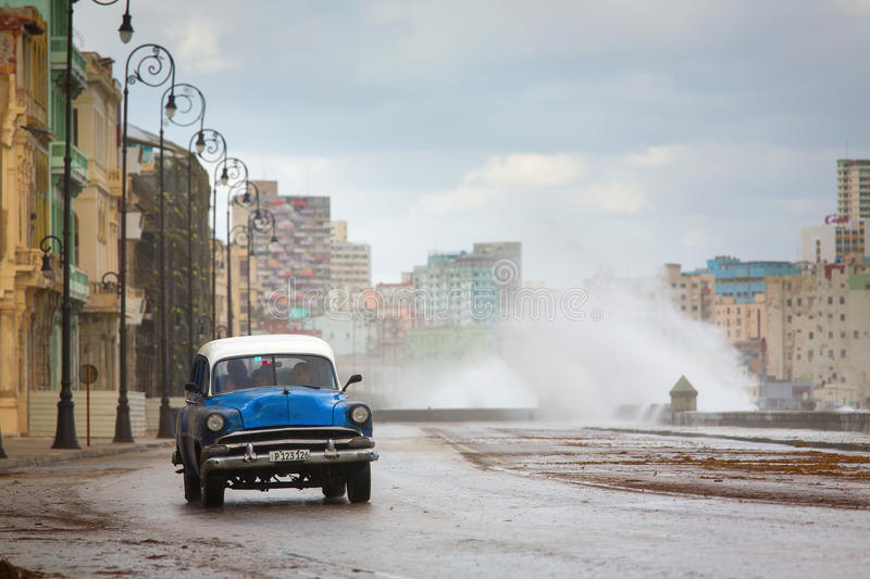 HAVANA - FEBRUARY 19: Classic car and antique buildings on February 15, 2015 in Havana. These vintage cars are an iconic sight. Of the island royalty free stock photography