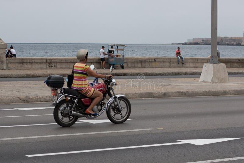 Havana, Kuba - 13. April 2017: Eine Frau f?hrt ein Motorrad entlang dem Malecon in Havana lizenzfreie stockfotos