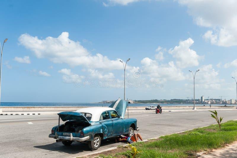 HAVANA, KUBA - 23. OKTOBER 2017: Havana Cityscape und Mann, die altes Auto auf der Straße reparieren stockfotografie