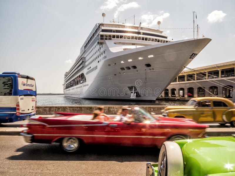 Classic car ride at Havana, Cuba. HAVANA - MARCH 30 2016: Unknown tourists rides a classic car in Old Havana, Cuba. Tourism industry in Cuba experimented a royalty free stock photo