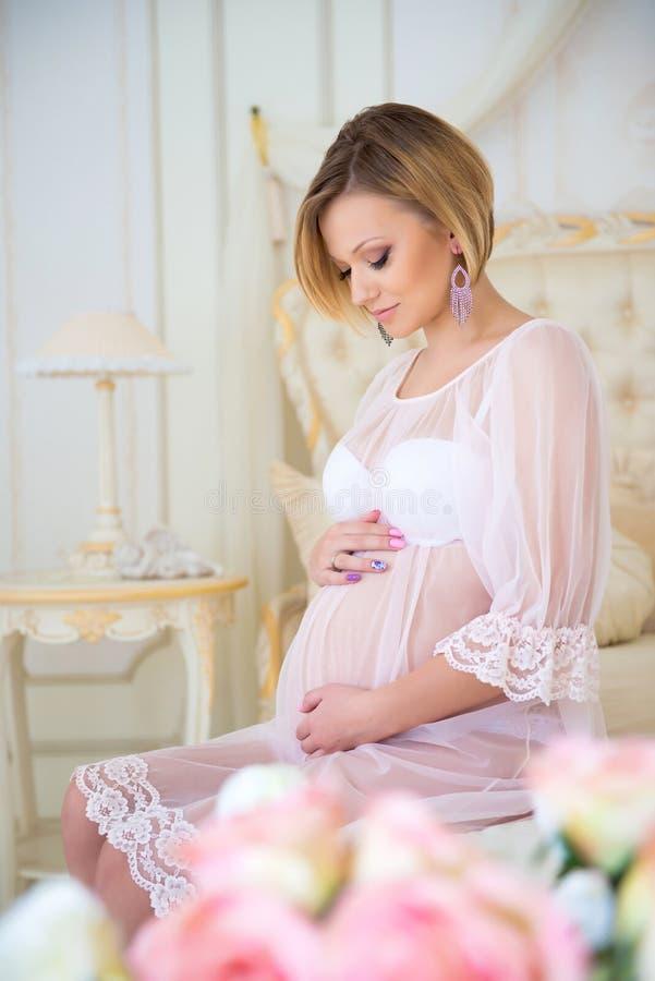 Havandeskap och att vänta på behandla som ett barn Gravid modersammanträde på en säng av rosor royaltyfri fotografi