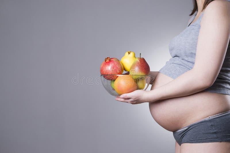Havandeskap och näring - gravid kvinna med frukt på grå bakgrund med kopieringsutrymme royaltyfria foton