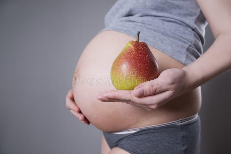 Havandeskap och näring - gravid kvinna med päronet i hand på grå bakgrund royaltyfri bild