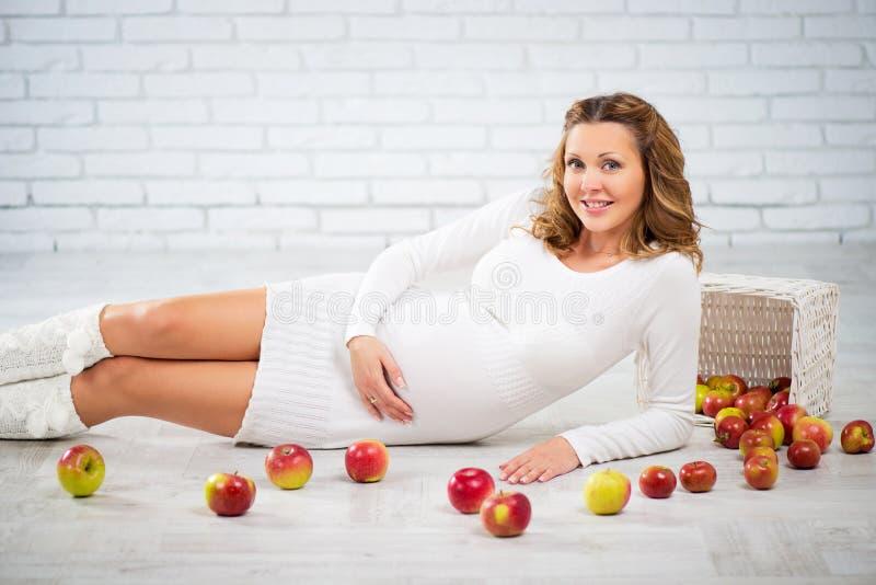 Havandeskap, sunt äta och folkbegrepp - som är nära upp av en lycklig gravid kvinna royaltyfri fotografi