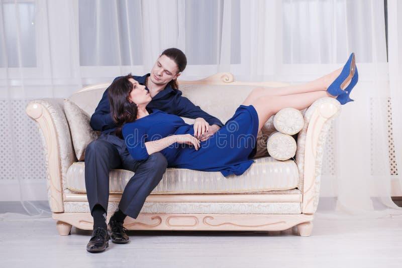 Havandeskapbarnpar på soffan royaltyfri fotografi