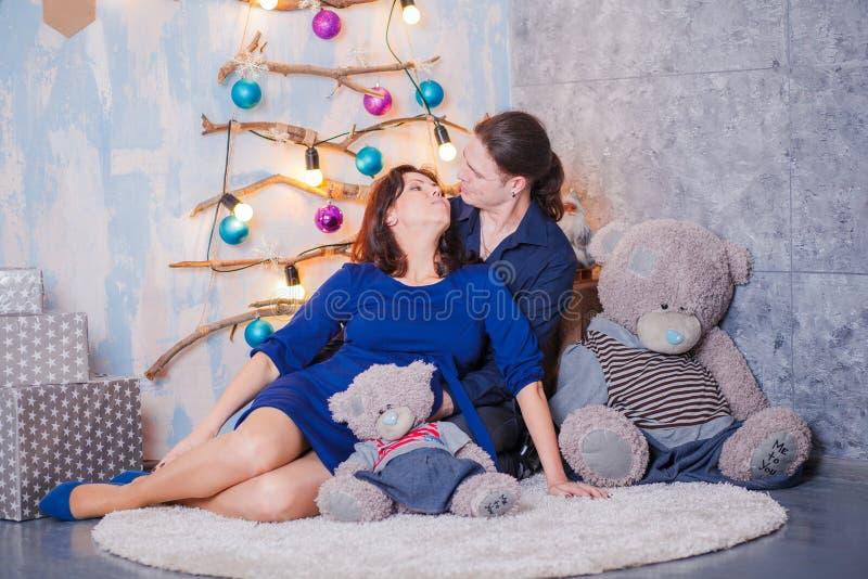 Havandeskapbarnpar på soffan royaltyfria foton