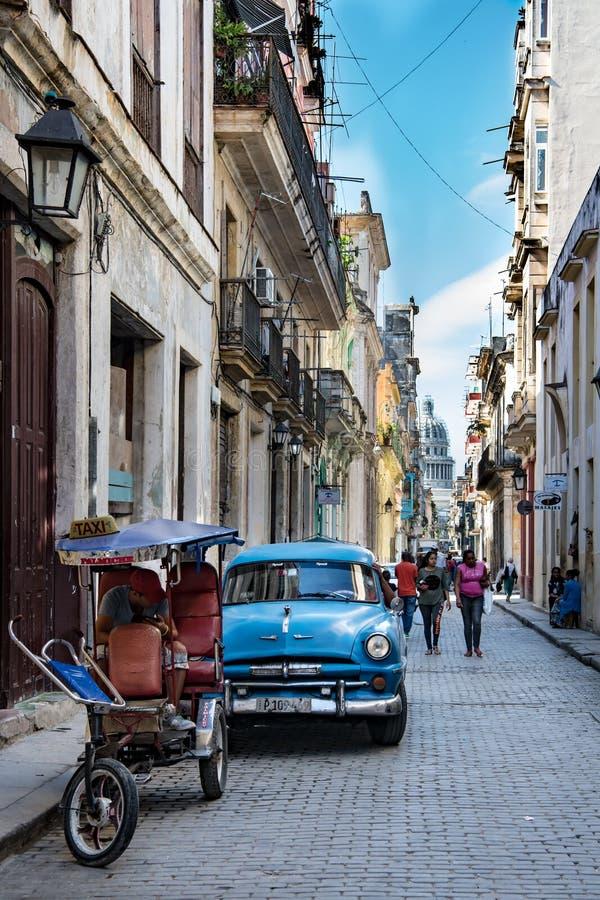 Havannacigarr klassisk bil i liten gata med sikt till Capitolio, Kuba fotografering för bildbyråer