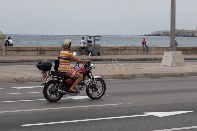 Havannacigarr Kuba - April 13, 2017: En kvinna k?r en motorcykel l?ngs Maleconen i havannacigarr royaltyfria foton