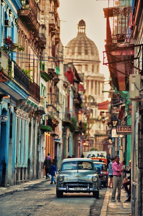 HAVANNACIGARR KUBA JANUARI 30, 2018: typisk tappningsikt av en gata av gamla havana, Kuba med folk och gamla bilar royaltyfri foto