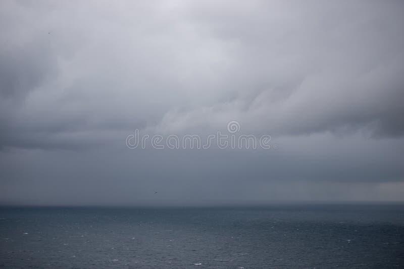 Havbakgrund med regnmoln arkivbild