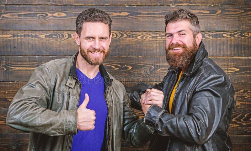 Have agreed. Brutal bearded men wear leather jackets shaking hands. Strong handshake. Friendship of brutal guys royalty free stock image