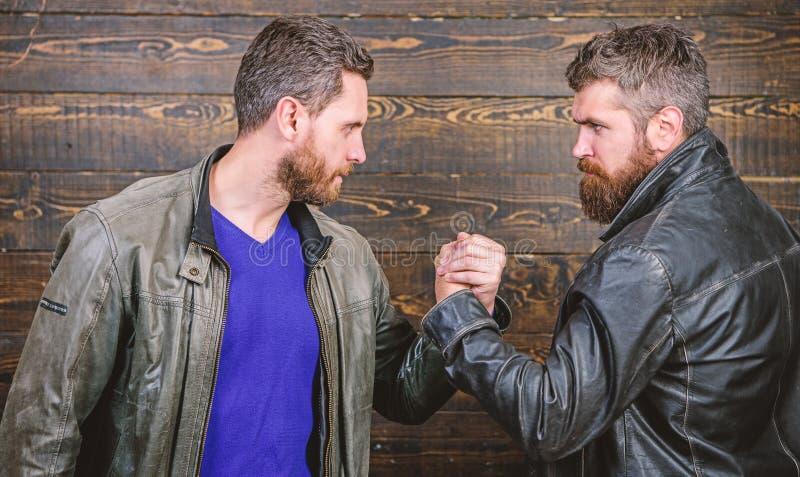 Have agreed. Brutal bearded men wear leather jackets shaking hands. Strong handshake. Friendship of brutal guys stock photography